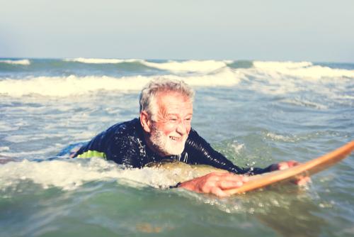 old man surfing ocean